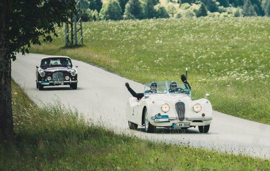 Oldtimer machen Spaß – wie man an den begeisterten Fahrern im Jaguar XK (Bj. 1954) sieht. Der Oldie wird von einem Aston Martin DB (Bj. 1955) gefolgt.
