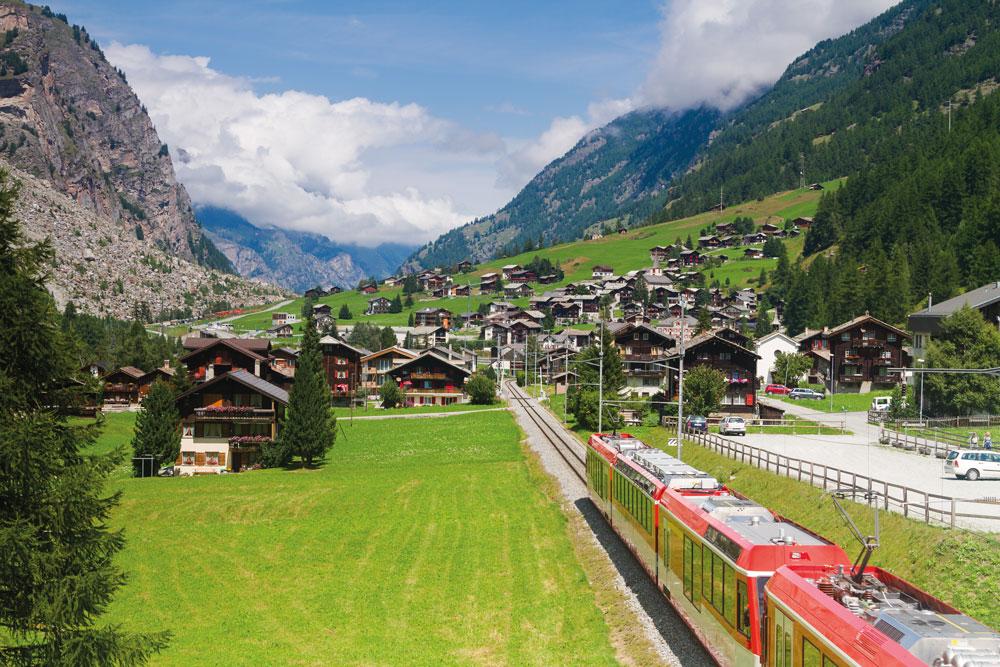 Bergpanorama und ganz viel Grün – der Zug durchquert ein alpines Hochtal.